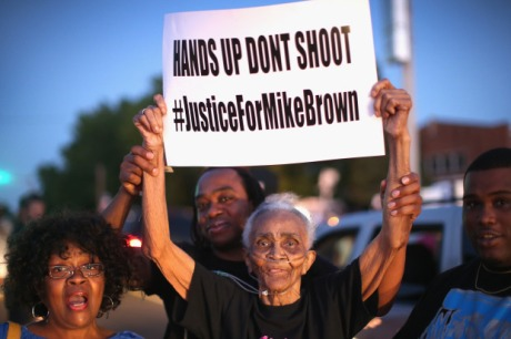 ST. LOUIS, MO - AUGUST 12:  Eighty-eight-year-old Creola McCalister joins other demonstrators protesting the killing of teenager Michael Brown outside Greater St. Marks Family Church while Browns family along with civil rights leader Rev. Al Sharpton and a capacity crowd of guests met inside to discuss the killing on August 12, 2014 in St Louis, Missouri. Brown was shot and killed by a police officer on Saturday, August 9, 2014 in the nearby suburb of Ferguson.   (Photo by Scott Olson/Getty Images)